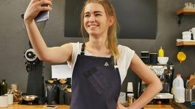 Barista femenino de Youg que toma el selfie en el lugar de trabajo fotografía de archivo