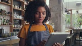Barista femenino sonriente usando la tableta digital en café almacen de video