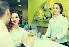 Barista femenino y dos clientes en café Imágenes de archivo libres de regalías