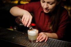 Barista femminile che fa una preparazione finale per il servizio del cocktail bianco delizioso immagini stock