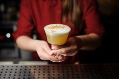 Barista femminile che serve un cocktail giallo decorato delizioso immagine stock