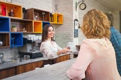 Barista femminile ed il cliente in un caffè Immagine Stock