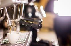 Barista gör kaffeespressoskottet, genom att strömma maskinen i kaffekafeteriastång royaltyfri bild