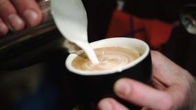 Barista gießt einen Cappuccino in eine Schale und zeichnet Muster auf dem Schaum stock video
