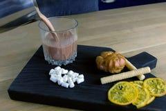 Barista giet cacao van waterkruik in rotsglas Kokende cacao Het proces van spijkers stock afbeelding