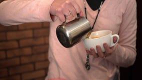 Barista giet koffie in de grote mok stock video
