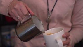 Barista giet koffie in een mok stock footage