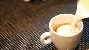 Barista gietende melk in hete koffie stock footage