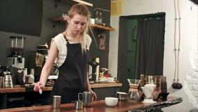 Barista grazioso che produce caffè al caffè, latte di versamento ad una tazza stock footage