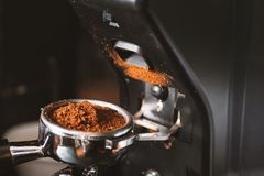 Barista grinding coffee beans using coffee machine, coffee grinder grinding freshly roasted make beans into a powder.  stock photos