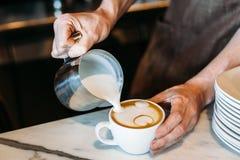 Barista hällande latteskum över kaffe, espresso och att skapa royaltyfria bilder