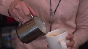 Barista häller kaffe in i en råna Arkivbilder