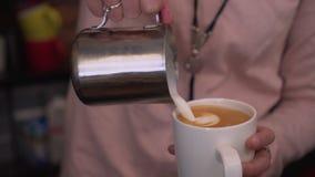 Barista häller kaffe in i en råna Arkivfoto