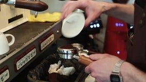 Barista häller nytt malt kaffe in i hållaren för att förbereda en espresso stock video