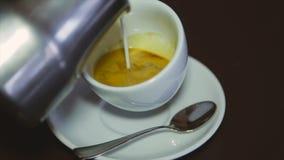 Barista häller nytt mjölkar in i kaffe cappuccino arkivfilmer