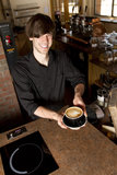 Barista Handing Cup from above. A barista hands you your cappuccino, focus is on cappuccino Royalty Free Stock Photo