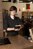 Barista Handing Cup Wide. A barista hands you your cappuccino, focus is on cappuccino Stock Photo