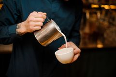 Barista hands pouring some milk into a coffee cup. Making latte art in a coffee shop Royalty Free Stock Photography