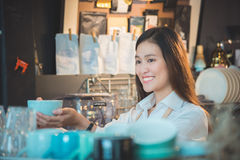 Barista holding coffee cup and smiles. Beautiful asian barista holding coffee cup and smiles in her coffee shop Royalty Free Stock Image