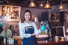 Barista holding coffee cup and smiles in her caf. Beautiful asian barista holding coffee cup and smiles in her cafe Royalty Free Stock Image