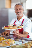 Barista holding a plate of pastries. In the bakery Royalty Free Stock Images