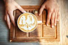 Barista holds cup of coffee with foam drawing. Male barista holds cup of coffee with foam drawing, top view, wooden cafe counter on background. Professional Royalty Free Stock Photography