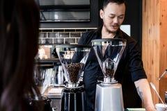 Barista joven que prepara el café de habas asadas grinded frescas foto de archivo
