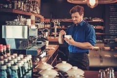 Barista kosztuje nowy typ kawa w jego sklep z kawą obraz stock