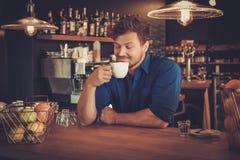 Barista kosztuje nowy typ kawa w jego sklep z kawą zdjęcia stock