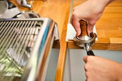 Barista loads the holder for the coffee machine stock photos