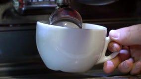 Barista maakt koffie De jonge barman brouwt koffie op de koffiemachine Langzame Motie De koffie giet in een witte kop sluit stock videobeelden