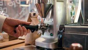 Barista maalt koffiebonen met molenmachine in de koffie, de bar of de winkel stock video