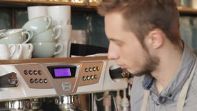 Barista makes coffee with a coffe machine stock footage