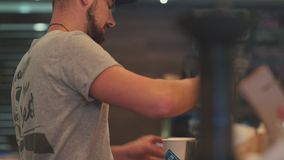 Barista makes a cup of coffee for the visitor. Coffee to go. stock footage