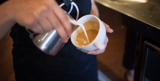 Barista makes latte art, focus in milk and coffee Stock Images