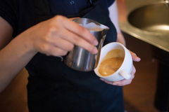 Barista makes latte art, focus in milk and coffee Royalty Free Stock Photos