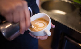 Barista makes latte art, focus in milk and coffee Stock Photography