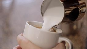 Barista makes pattern in coffee bar. Close-Up stock footage