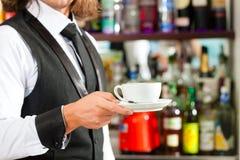 Barista making cappuccino in his coffeeshop Stock Photo