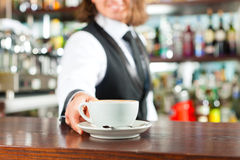 Barista making cappuccino in his coffeeshop royalty free stock photography