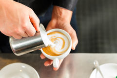 Barista making cappuccino in his coffeeshop Royalty Free Stock Images