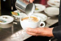 Barista making cappuccino in his coffeeshop Stock Image