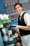 Barista Making Coffee. A young and attractive barista making a coffee in an indoor restaurant Royalty Free Stock Image