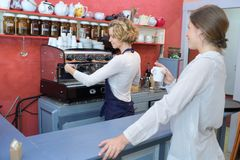 Barista making coffee at bar with female client. Barista making coffee at the bar with female client Stock Photos