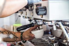 Barista making coffee. By coffee machine Royalty Free Stock Photos