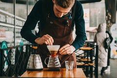 Barista making coffee in coffeeshop. Barista making filter coffee in coffeeshop outdoors Stock Photography