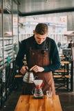 Barista making coffee in coffeeshop. Barista making filter coffee in coffeeshop outdoors Royalty Free Stock Photos