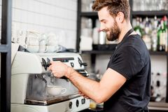 Barista making coffee. Handsome barista making coffee with coffee machine at the bar of the modern cafe Royalty Free Stock Photo