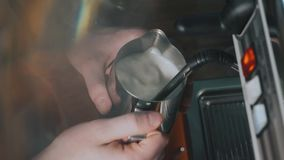 Barista making coffee in coffee machine at a busy coffee shop. Coffee flows from cofee machine in slow motion stock video
