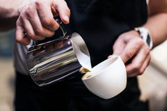 Barista making coffee pouring milk Stock Photography